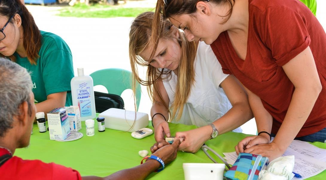 A student measures the sugar level of a local man during her Public Health internships in the Philippines.